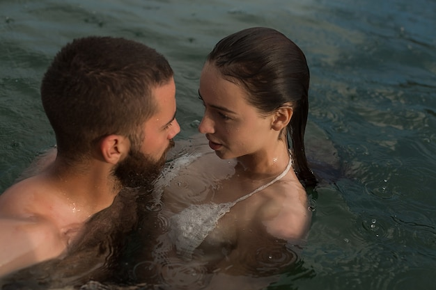 Beautiful couple in love romantically hug and kiss in the sea. vacation on the sea on the beach, honeymoon, relationships.