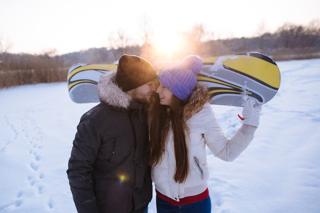 Beautiful couple in love of snowboarders in a frosty winter day. close up portrait.