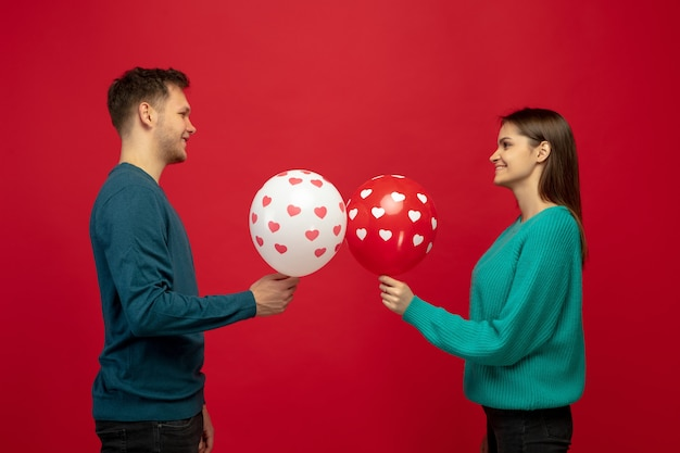 Beautiful couple in love with balloons on red studio wall