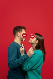 Beautiful couple in love with lollipops on red studio wall