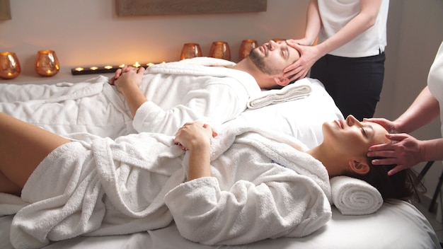 Beautiful couple lying down on massage beds enjoying a head massage in luxury spa.
