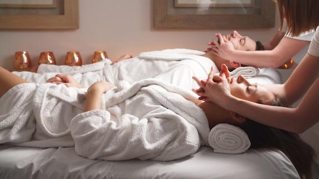 Красивая пара, лежа на массажных кроватях, наслаждаясь массаж головы в роскошном спа-салоне.