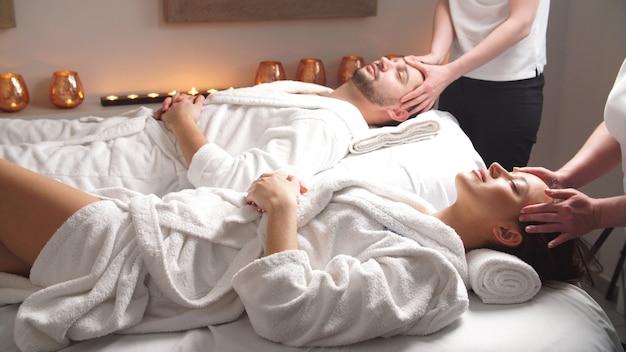 高級スパでヘッドマッサージを楽しんでいるマッサージベッドに横たわって美しいカップル。