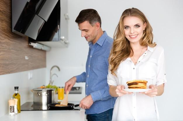 キッチンで一緒に朝食のパンケーキを作る美しいカップル
