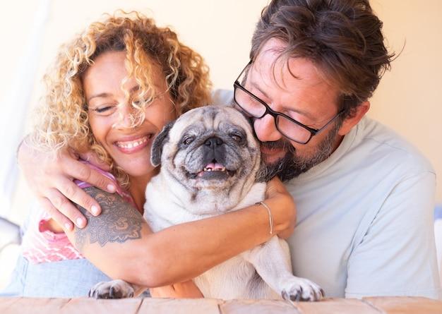 彼らの明確なパグ犬に恋をしている美しいカップルの男性と女性永遠の友人