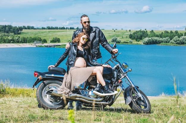 背景のオートバイの美しいカップルの男性と女性
