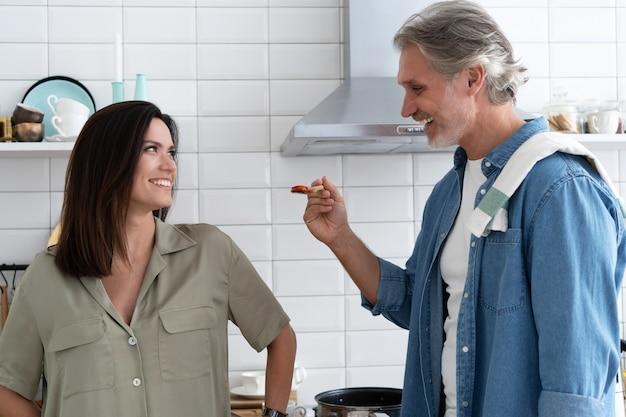 아름다운 커플. 집에서 부엌에서 요리하면서 아내에게 먹이를 주고 웃고 있는 남자
