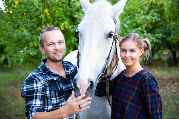Beautiful couple man and girl with a horse in country style