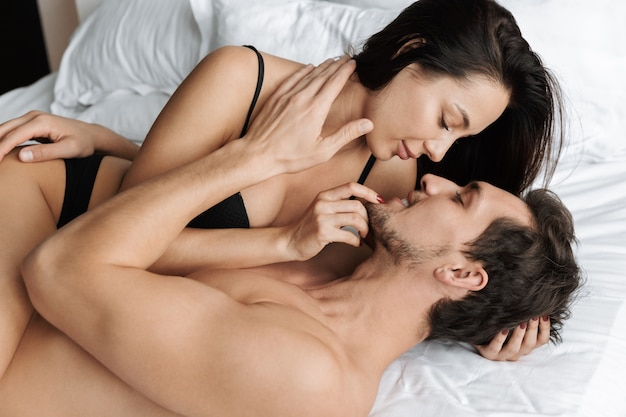 Beautiful couple man and woman hugging together, while lying in bed at home or hotel apartment
