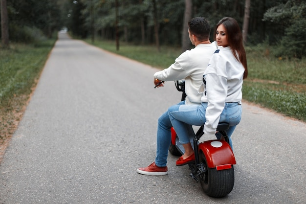 Beautiful couple man and woman ride on a modern electric bike in the park