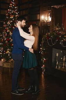 Красивая пара, модельная женщина в юбке в объятиях бородатого красавца возле елки