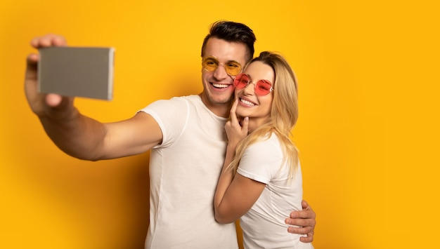 A beautiful couple in multicolored sunglasses is hugging each other and smiling while taking selfie on their smartphone