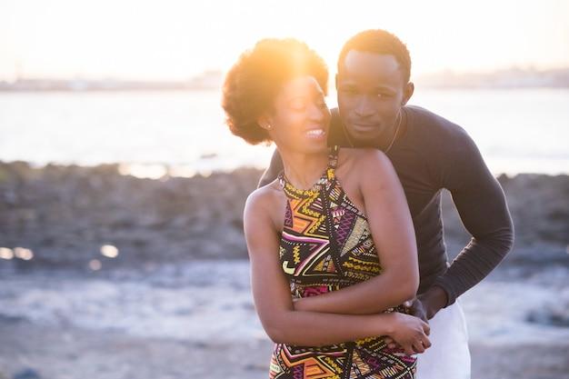 伝統的なドレスを着た黒人人種のアフリカ人モデルの美しいカップルは、夏の日没時にビーチで楽しみ、愛し合う