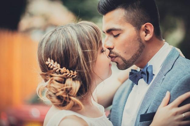 結婚したばかりの美しいカップルがたくさんの愛を込めてお互いにキスします