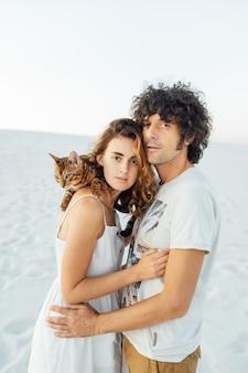 Красивая пара влюбленных обнимают друг друга и держат кошку на руках