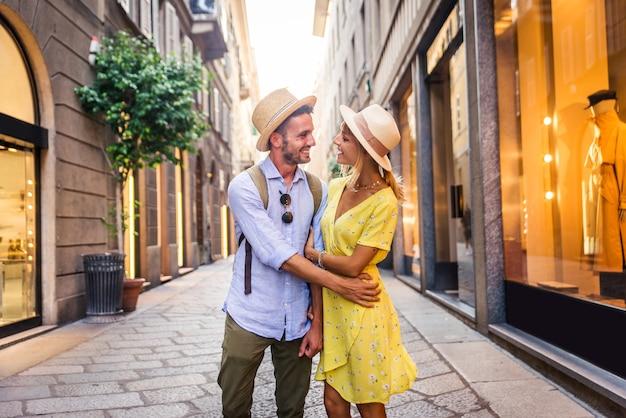 도심에서 쇼핑하는 연인의 아름다운 커플. 유명한 유럽 도시를 방문하는 장난기 많은 관광객