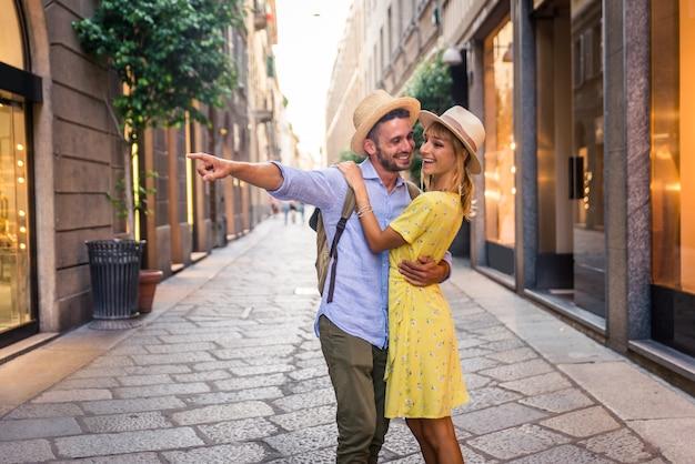 도심에서 쇼핑하는 연인의 아름다운 커플. 유명한 유럽 도시를 방문하는 장난기 많은 관광객 프리미엄 사진