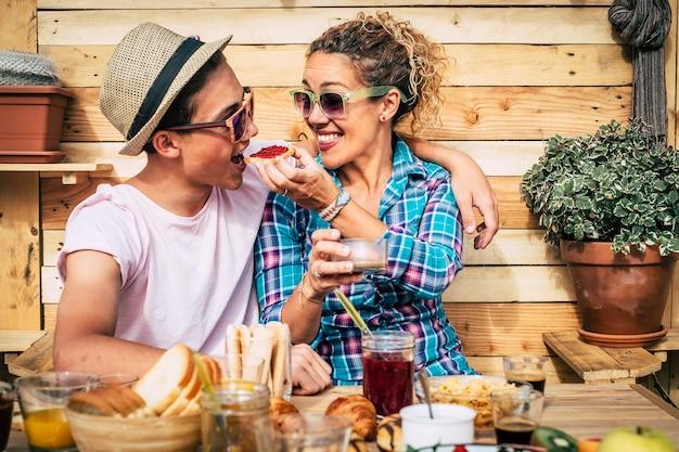お母さんと息子の美しいカップルが一緒に家のテラスで楽しんで笑って食べています---幸せで面白い帽子をかぶった男
