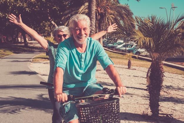 シニアと成熟した結婚の美しいカップル、タンデム自転車に乗って、素晴らしい晴れた日を楽しんでいます-女性と男性