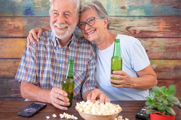 맥주와 팝콘으로 즐거운 시간을 보내는 아름다운 노인 부부는 나무 테이블에 앉아 웃고 있다