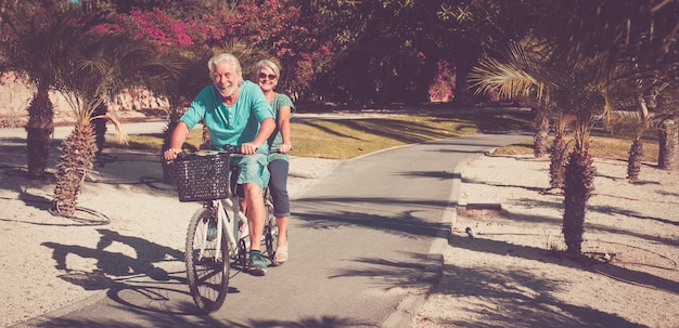 植物と手のひらのある素晴らしい公園で一緒に楽しんでタンデムに乗っている先輩の美しいカップル-自転車に乗って笑っている幸せな2人の成熟した人々