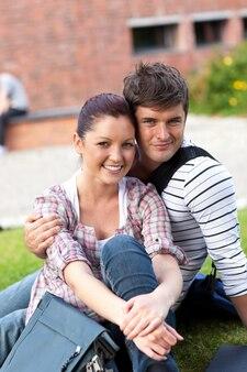 草の上に座ってカメラで笑っている学生の美しいカップル