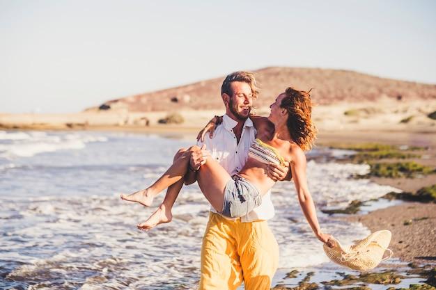 男性の腕に女性と砂の上を歩いているビーチで2人の大人の美しいカップル-ビーチで彼の妻を保持している男性