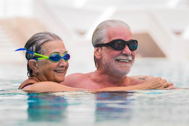 수영장에서 함께 즐거운 시간을 보내는 두 노인의 아름다운 커플 - 사랑으로 웃고 있는 남편을 안고 있는 여성