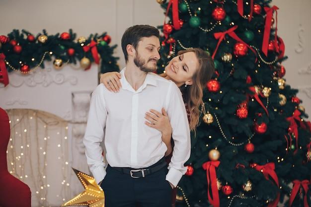 若い恋人たちの美しいカップルが自宅で屋内を抱いています。