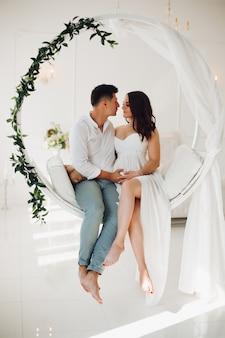 Красивая пара молодых людей, сидя на белом качели