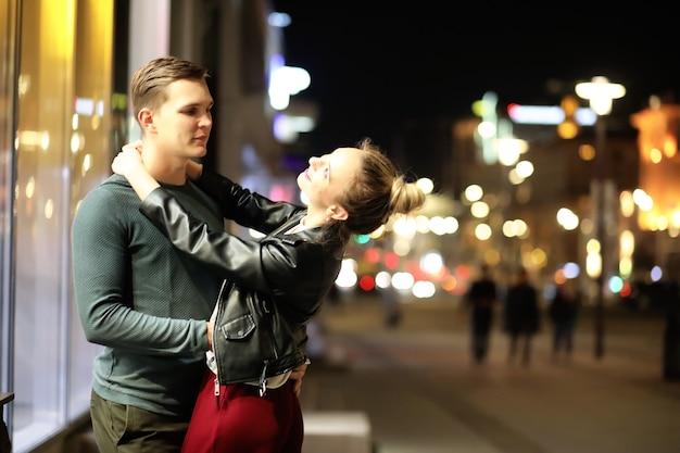 屋外の夜の街でデートの美しいカップル