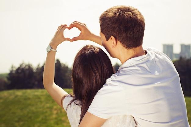 ハグと心のジェスチャーを作る公園で歩いている日に美しいカップル