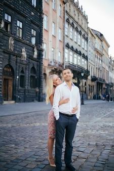 完全な高さをポーズ都市背景に美しいカップル