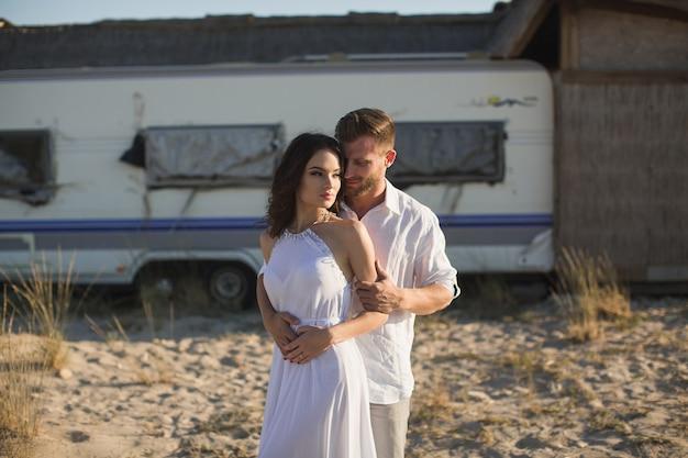Красивая пара на пляже, на фоне фургона.