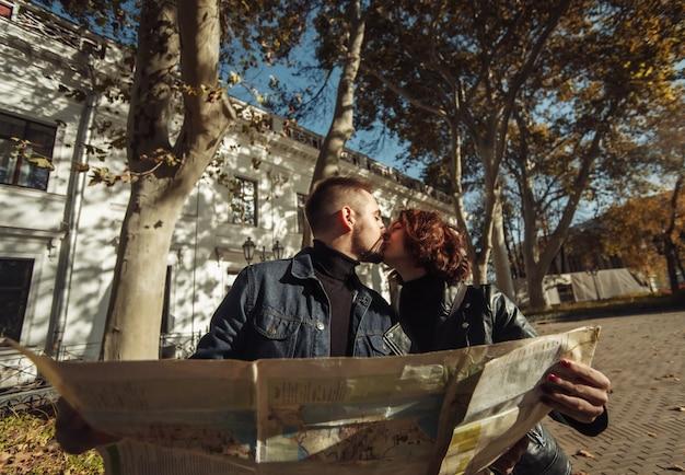 道順とキスのために紙の市内地図を使用して休暇中の美しいカップル