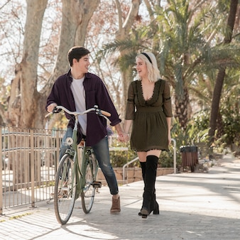 Beautiful couple at the park withbicycle
