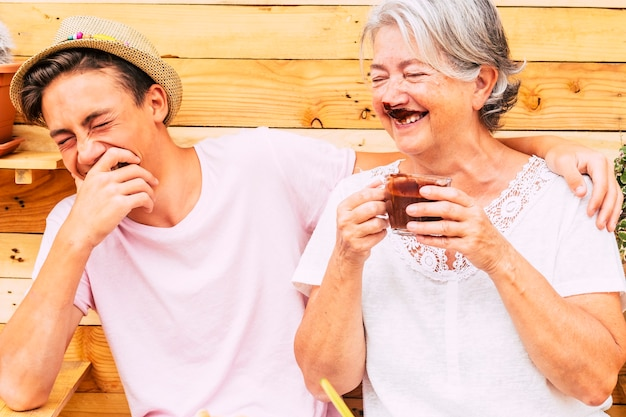Beautiful couple of people having fun and joking together with a grandma drinking hot chocolate