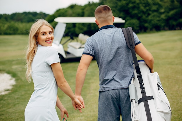 ゴルフコースでゴルフをする美しいカップル
