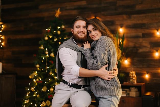 クリスマスツリーを背景にポーズをとる美しいカップル。ガールフレンドと抱き合ってカメラを見て幸せな男。