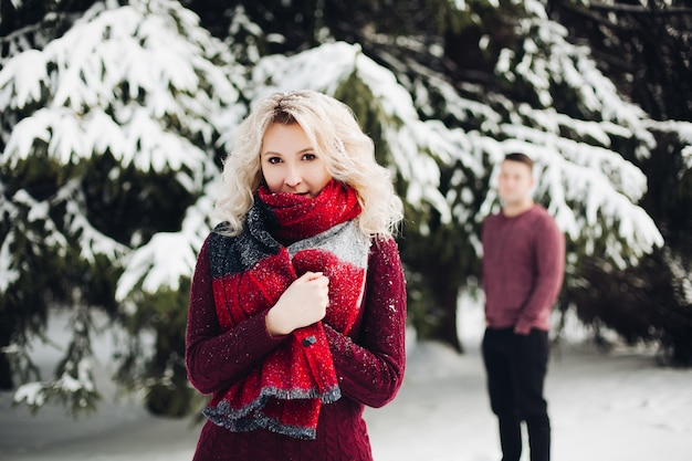 Beautiful couple posing in winter forest and looking at camera.