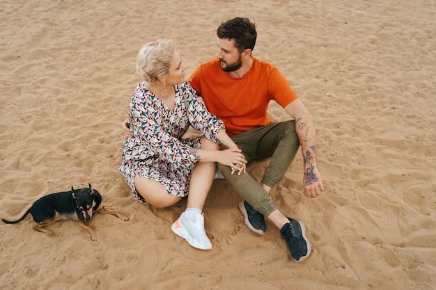 陽気な犬と遊んでいる間ハグとキスの砂でリラックスした美しいカップル