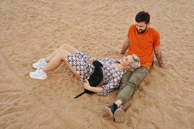 Красивая пара расслабляется на песке, обнимается и целуется, играя со своей позитивной собакой