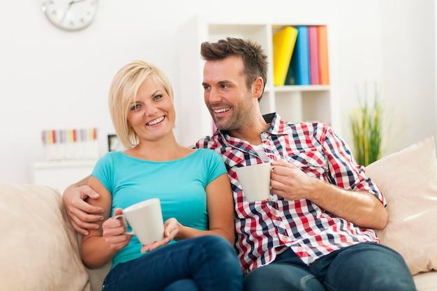 一杯のコーヒーとソファでリラックスした美しいカップル