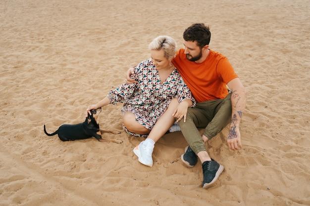 Belle coppie che si rilassano sulla sabbia che si abbracciano e si baciano mentre giocano con il loro cane positivo