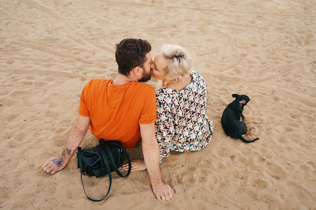 Beautiful couple relaxing on sand hugging and kissing while playing with their positive dog