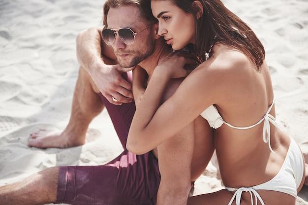 Una bella coppia che si distende sulla spiaggia sabbiosa, indossando abiti da bagno. atmosfera romantica.