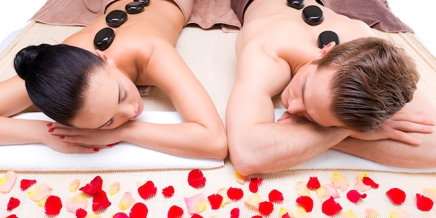 Beautiful couple relaxing in spa salon with hot stones on body. beauty treatment therapy.