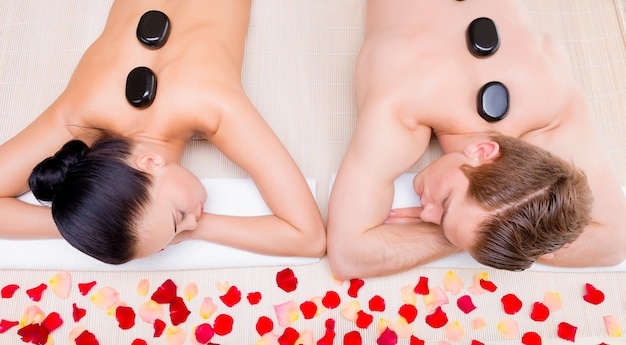 Belle coppie che si rilassano nel salone della stazione termale con pietre calde sul corpo. terapia di trattamento di bellezza.