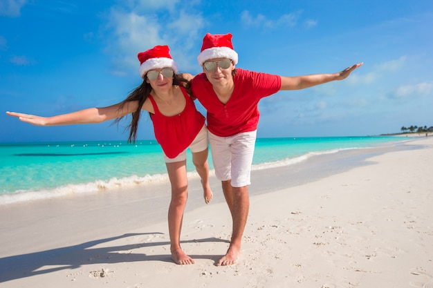 Beautiful couple in santa hats on tropical beach have fun