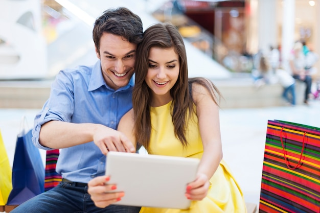 Beautiful couple in shopping mall looking on digital tablet